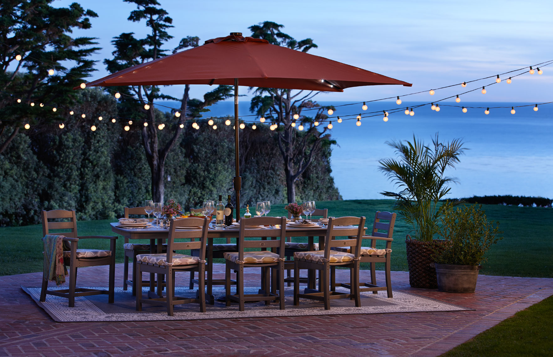 Wood outdoor furniture with red umbrella at dusk on patio by the ocean