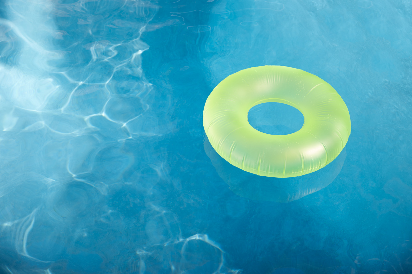 Green inflatable donut floatie sitting in blue pool San Francisco architectural photographer