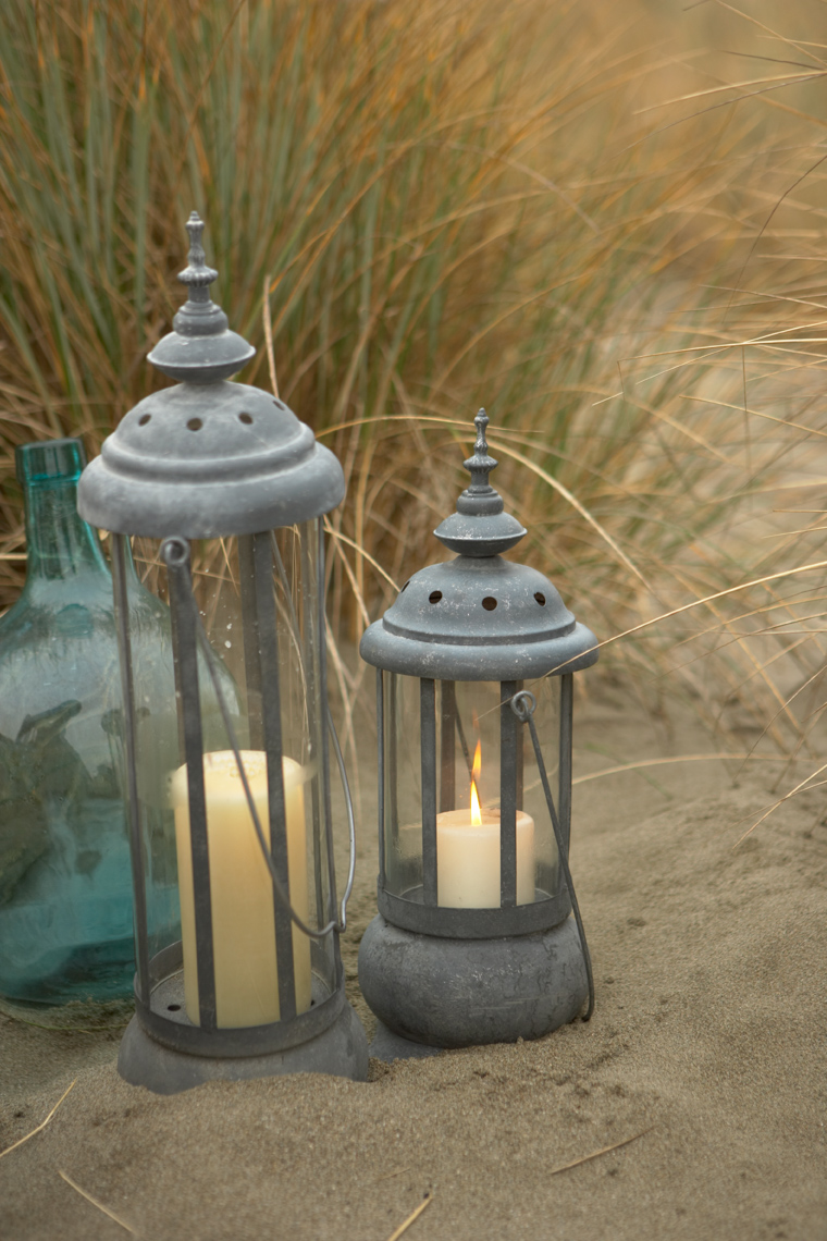 Tal outdoor lanterns with glass fronts in the sand with beach grass