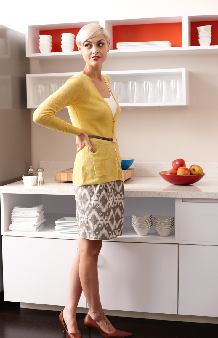 blonde woman in chic yellow top in front of sleek white kitchenware with accents of red