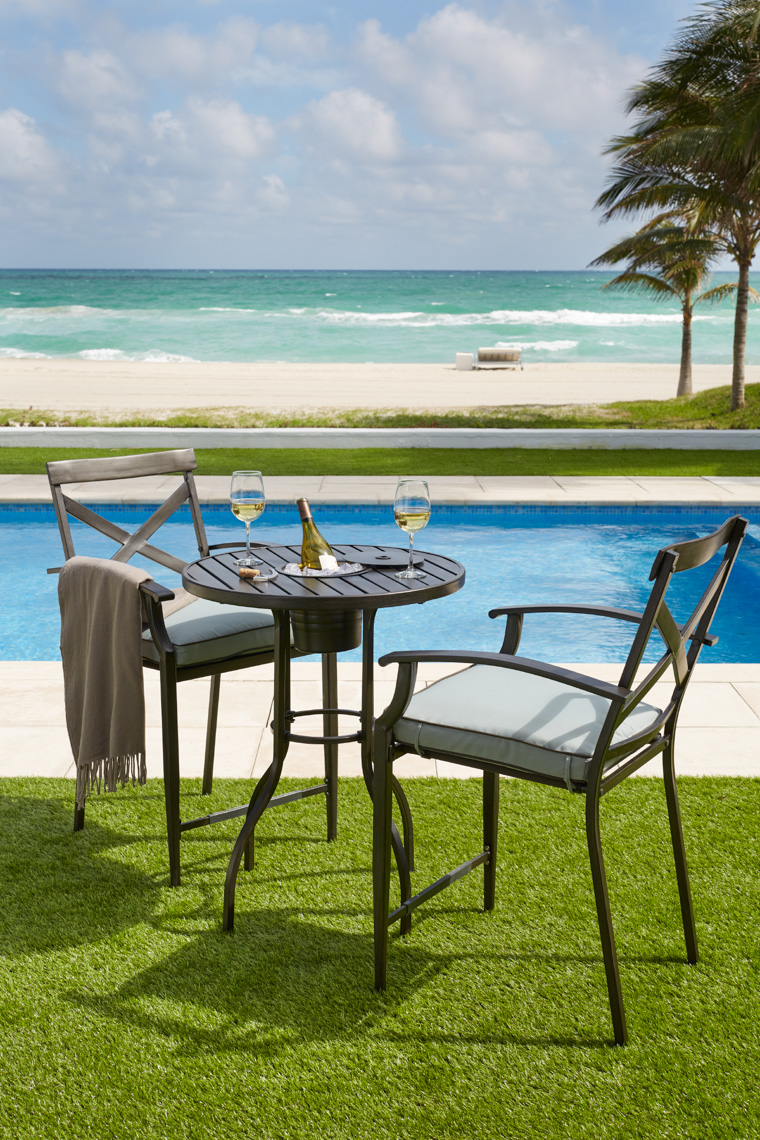 Two Black metal chairs and table on green lawn near pool