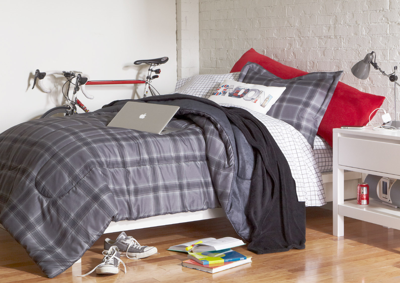 bedroom with plaid grey and red bedding with white walls and laptop and shoes and stack of books