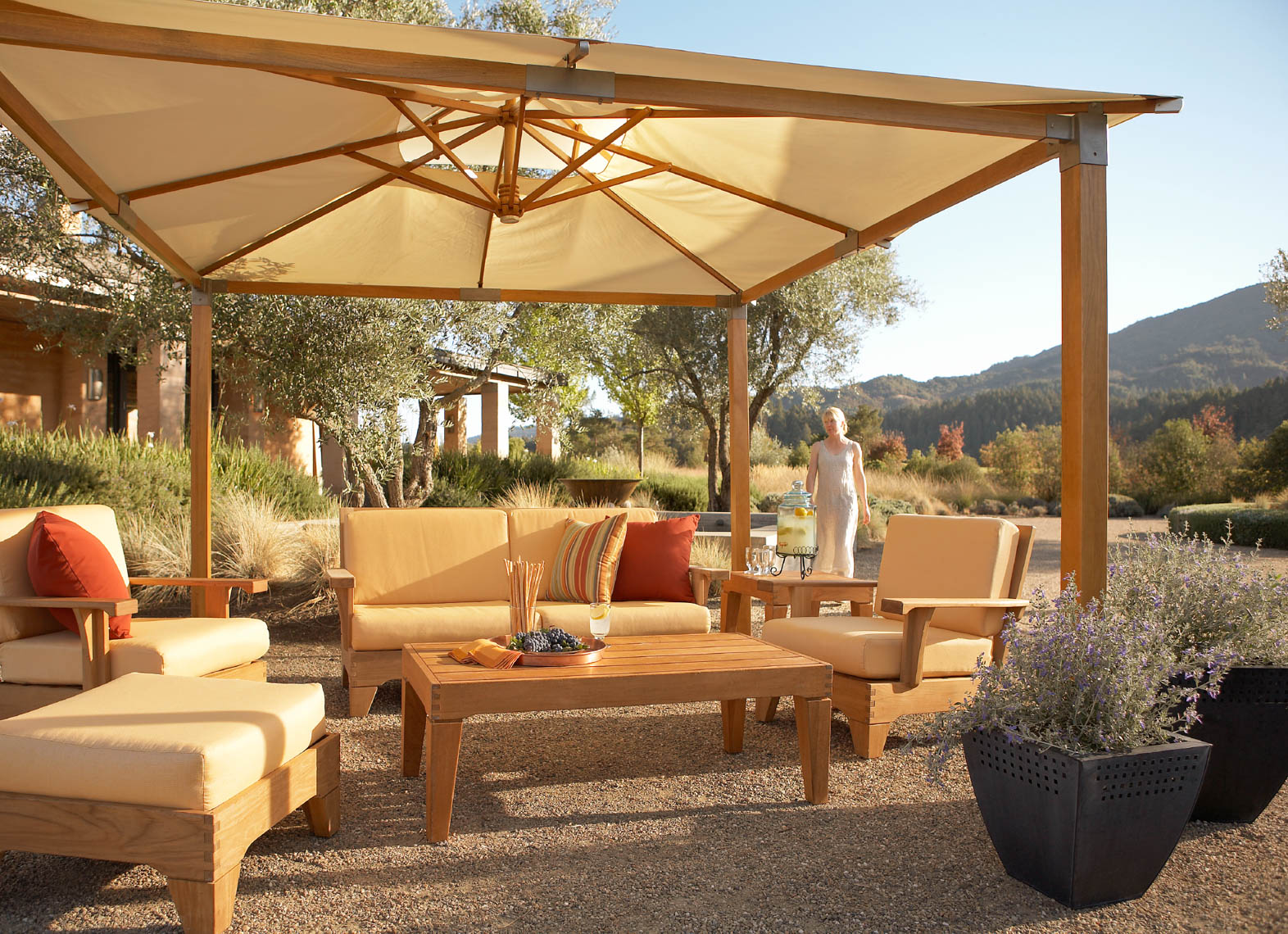 outdoor teak furniture with cushions and furniture under canvas canopy in pea gravel