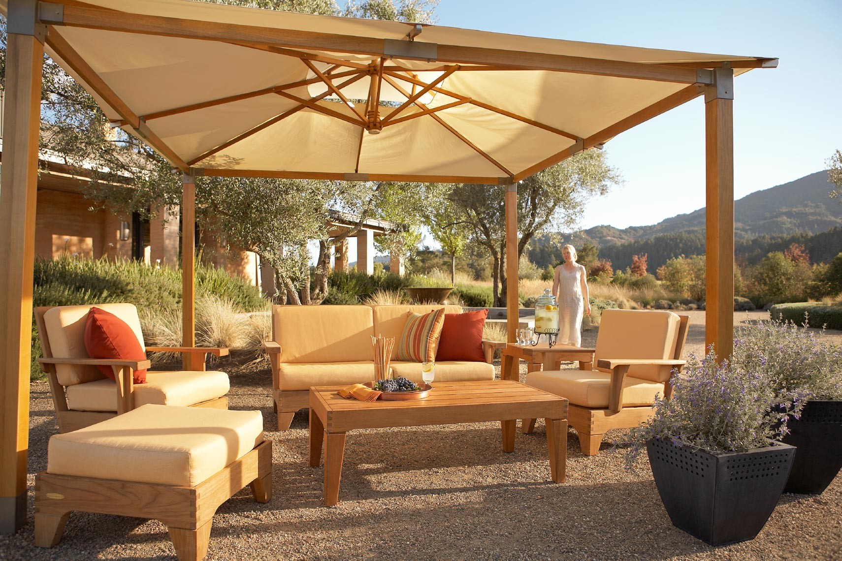 Teak furniture collection with large canvas structure on outdoor patio