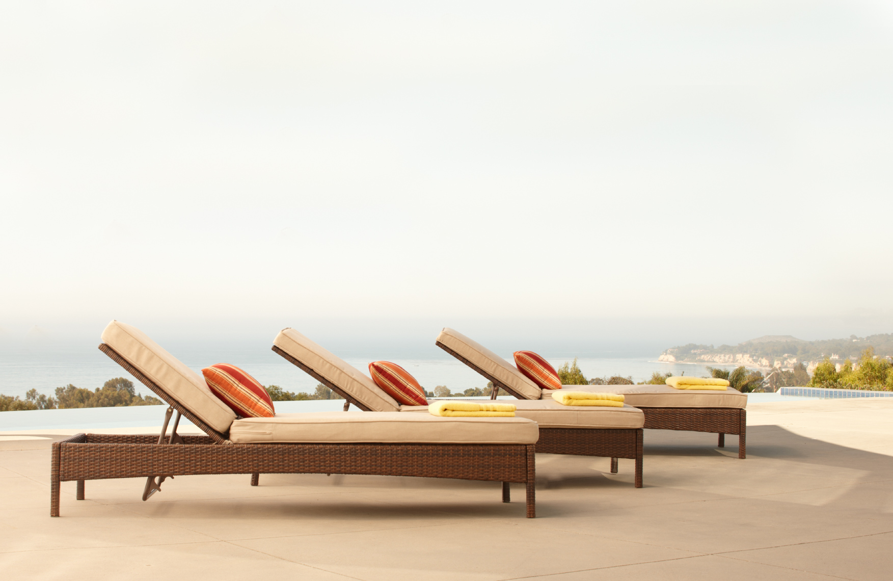 3 brown wicker chaises with cushions lined up on patio San Francisco architectural photographer