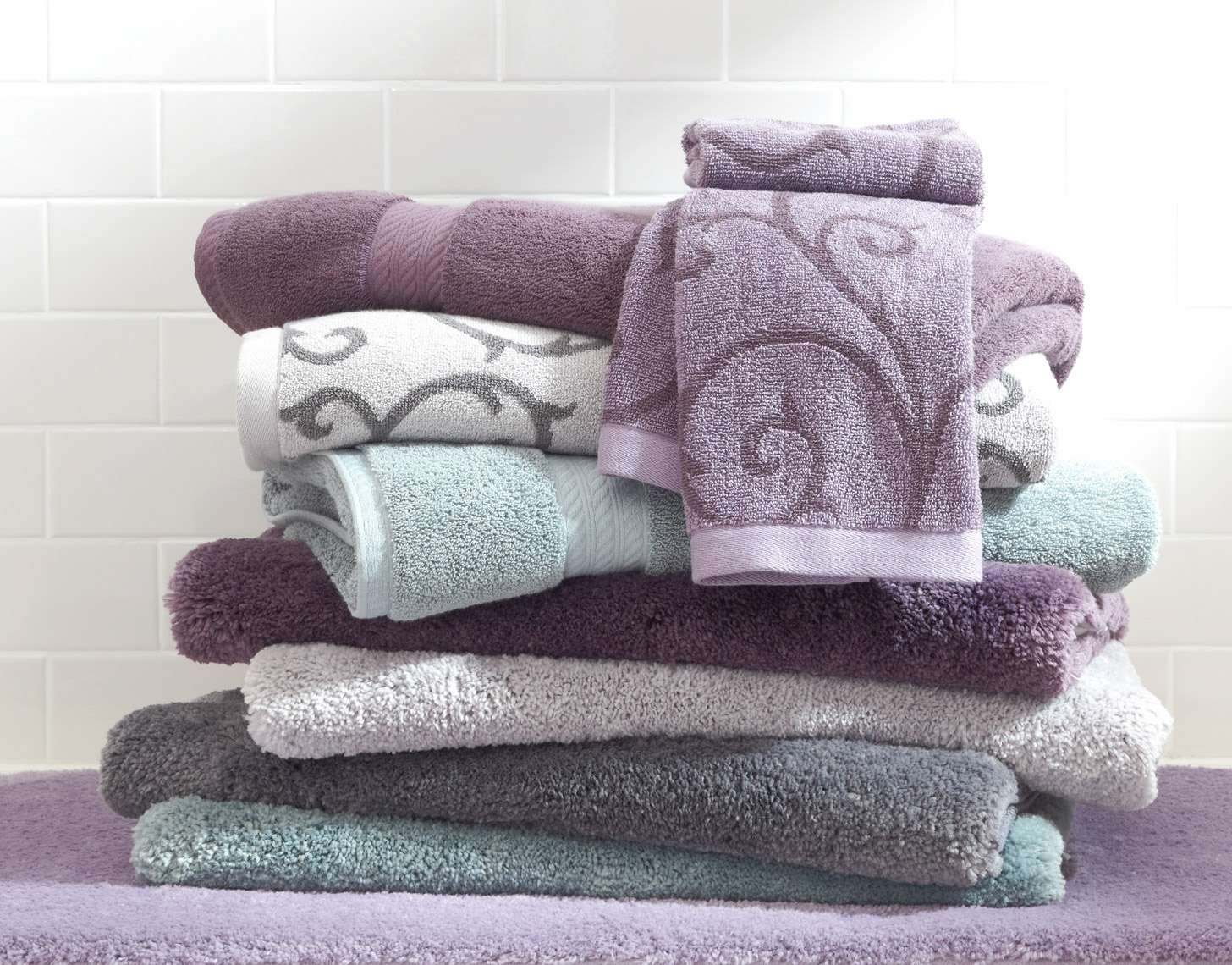 stacked plum and grey and teal towels on purple bathmat with white tile walls