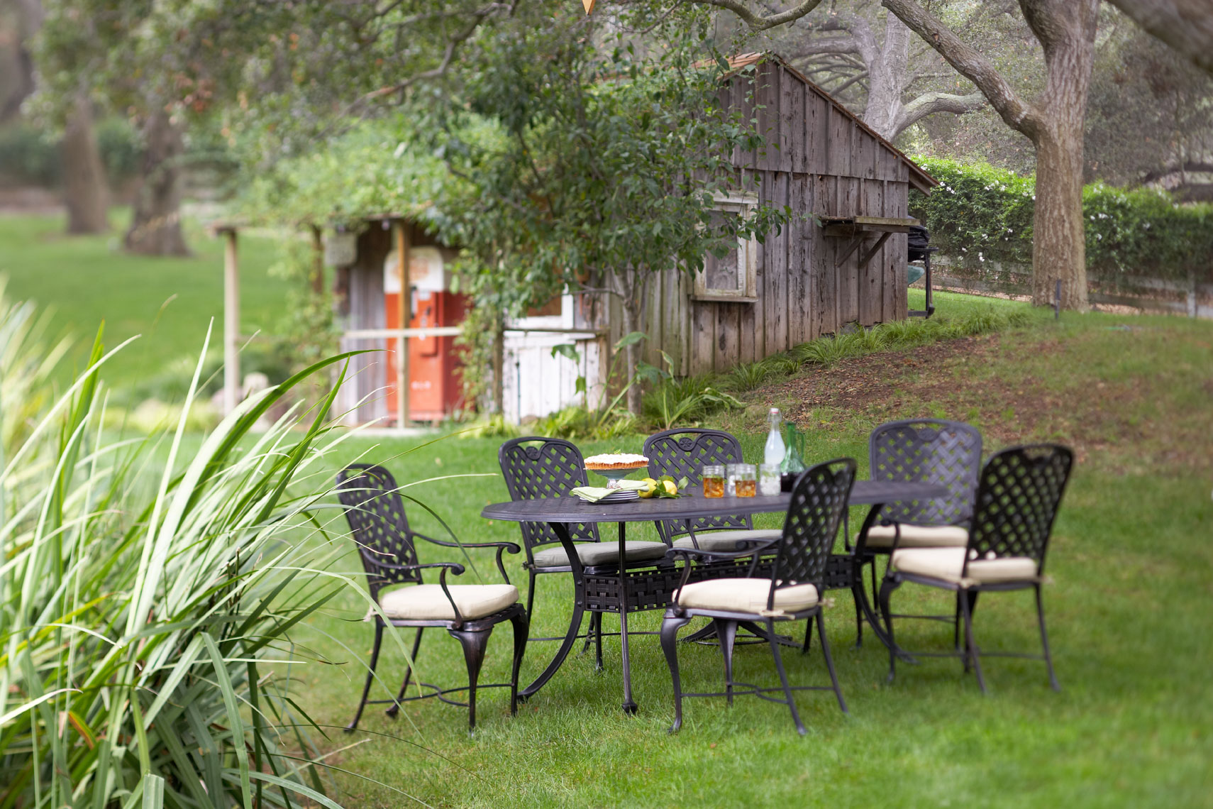 Black metal dinning set on green lawn with old shed