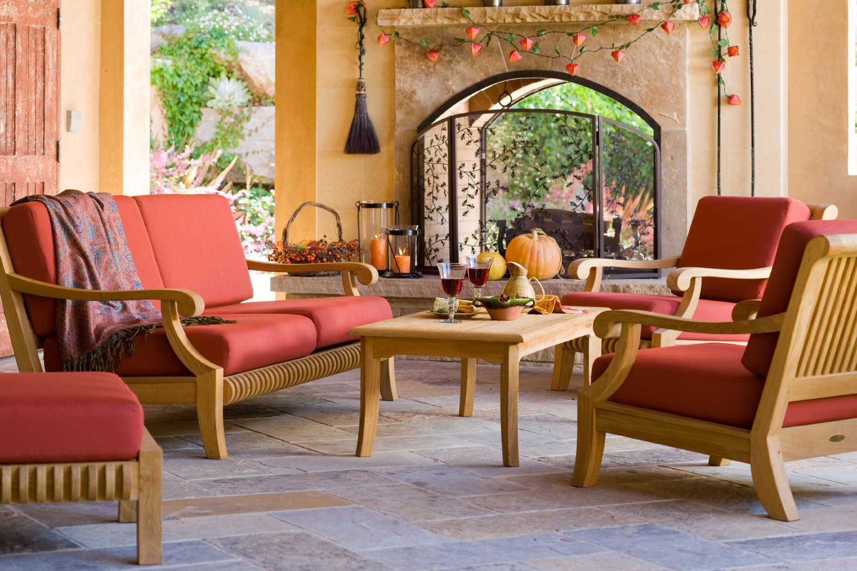 Teak lounging collection with red cushions on patio with fireplace