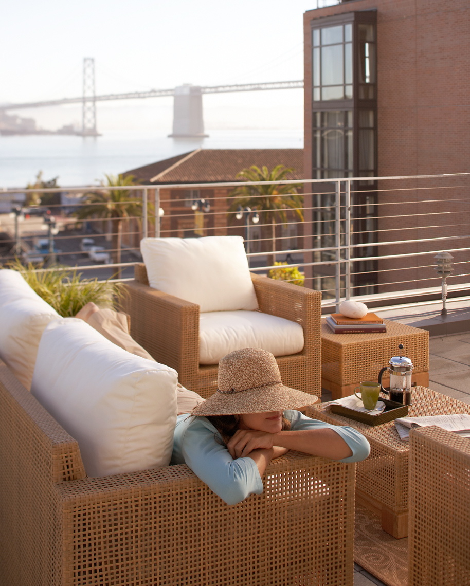 woman in sun hat lying on wicker patio furniture with white pillows on rooftop with Bay Bridge view