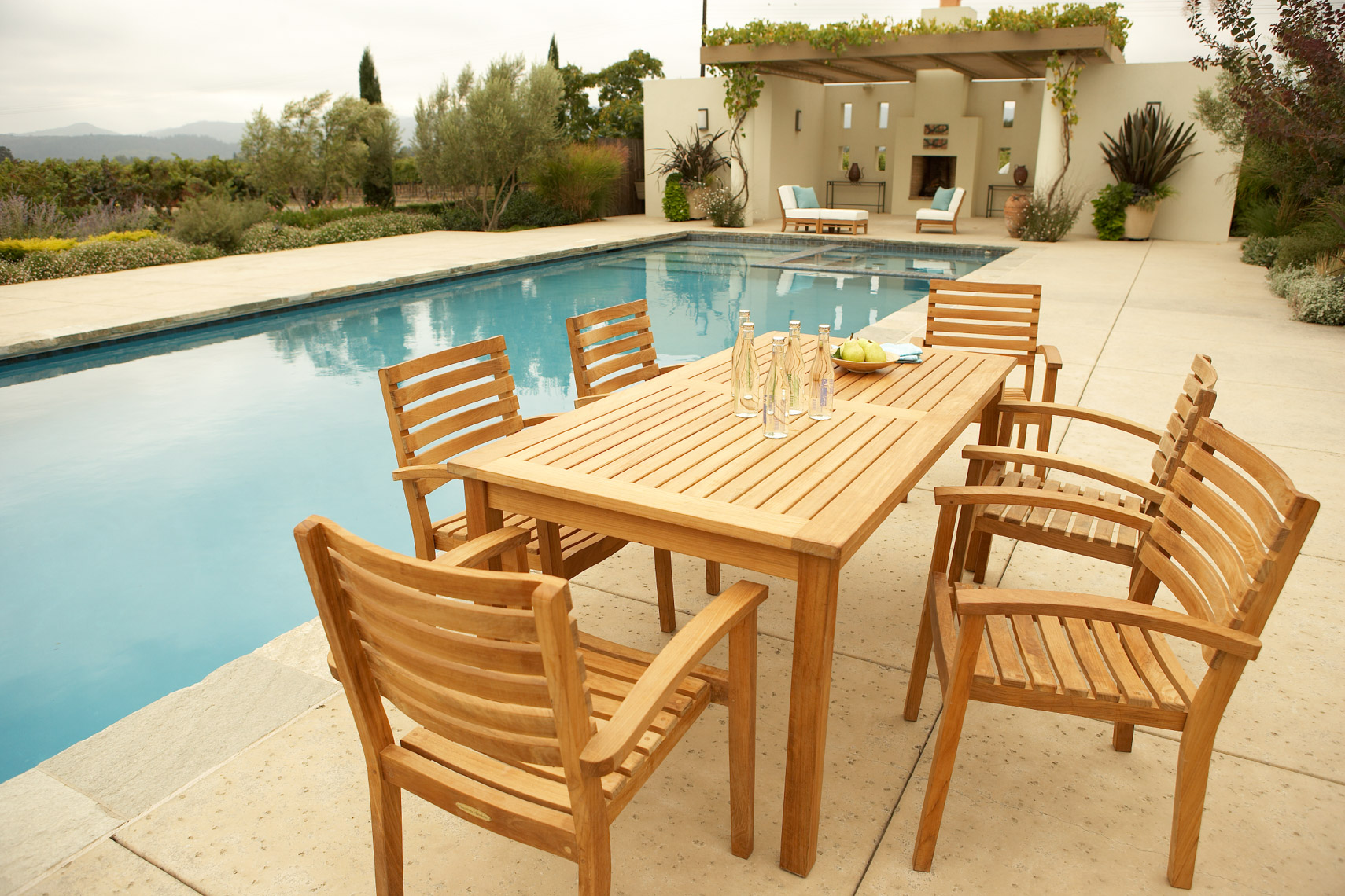 Teak dining collection on tile patio by pool