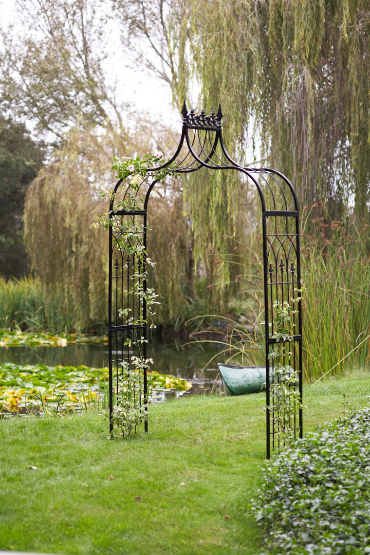 Black metal garden arch in green grass by pond