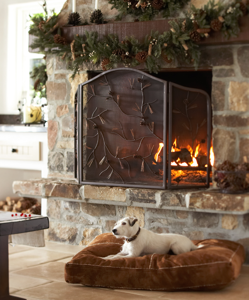 white dog on brown floor cushion with holiday decorated fireplace San Francisco interior photographer