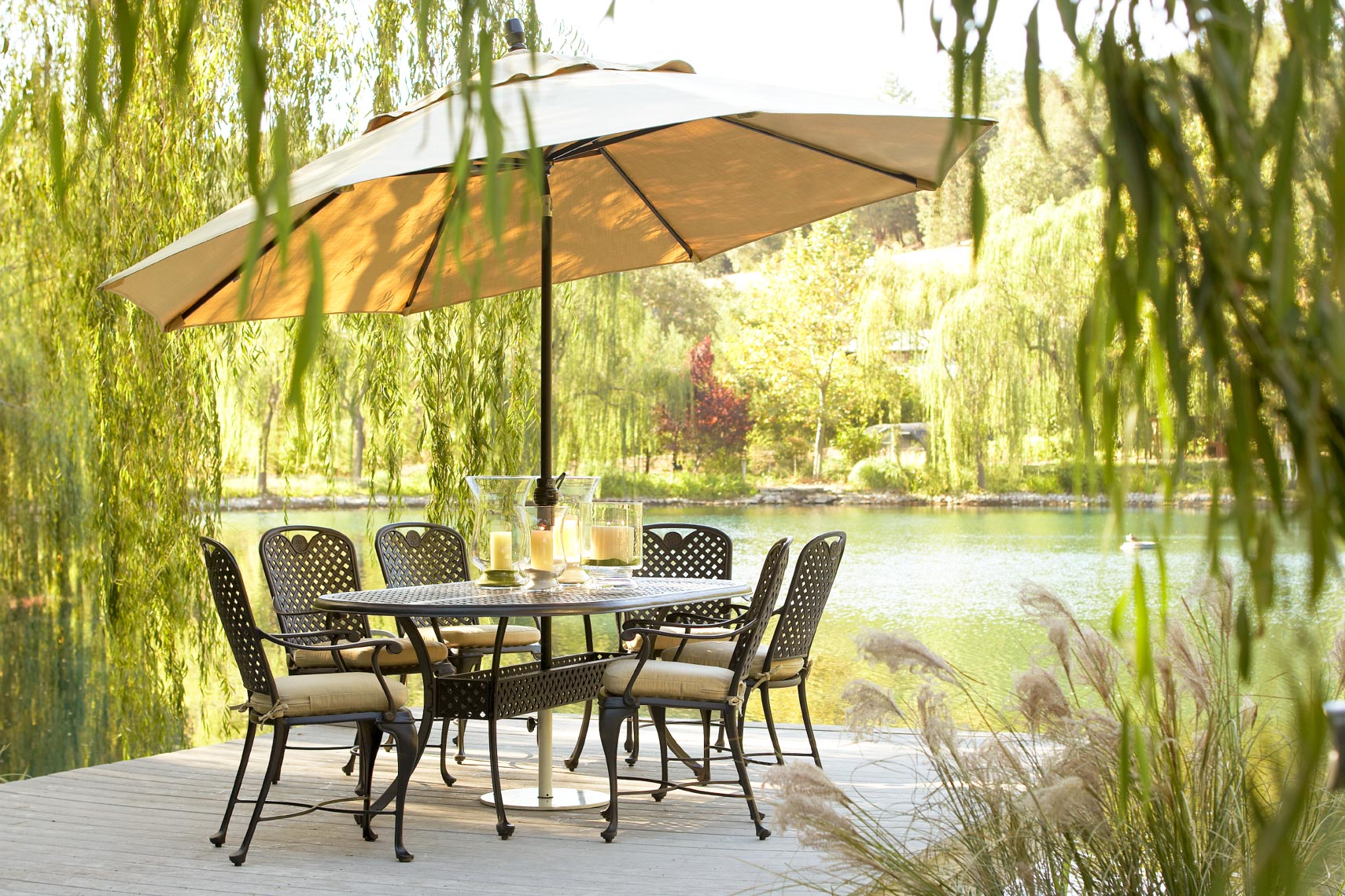 Metal furniture and table with umbrella on dock by water