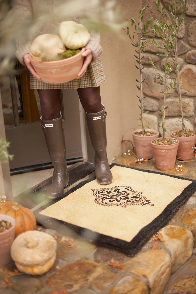 Woman in garden boots entering home with basket