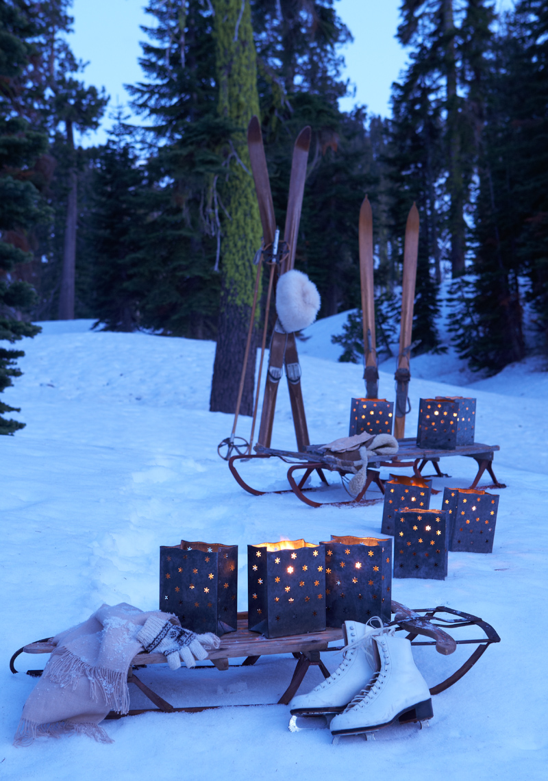 Snow scene of ice skates and sled and luminary at night