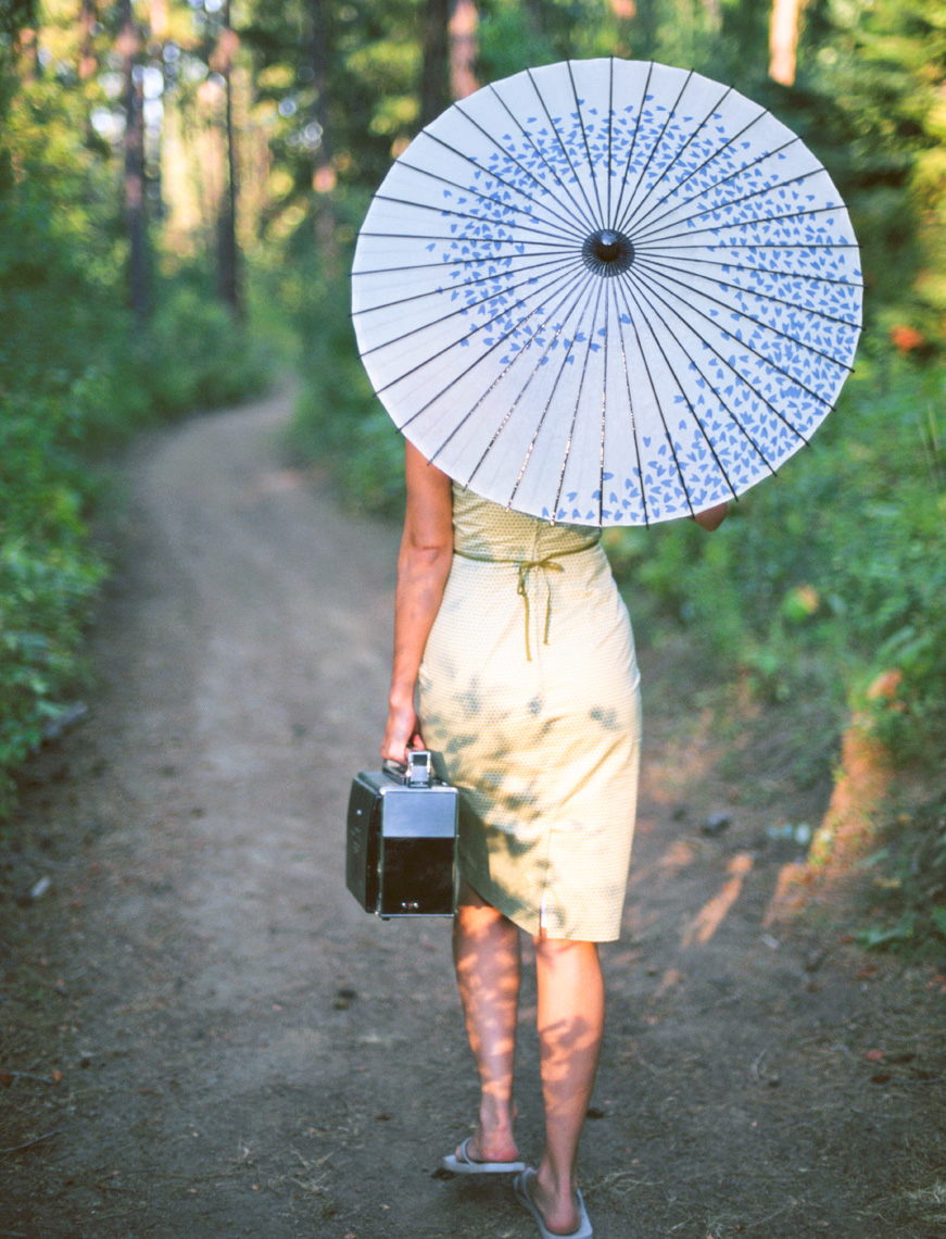 Woman in tight green dress seen from behind walking down a dirt path with a blue paper parasol and vintage radio