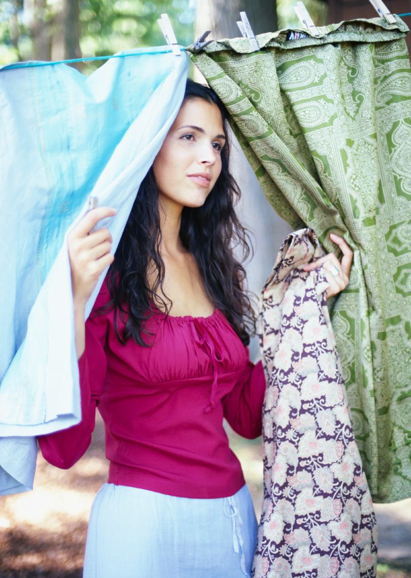 Attractive woman in purple top and blue skirt peaking through colorful linens hanging to dry outside