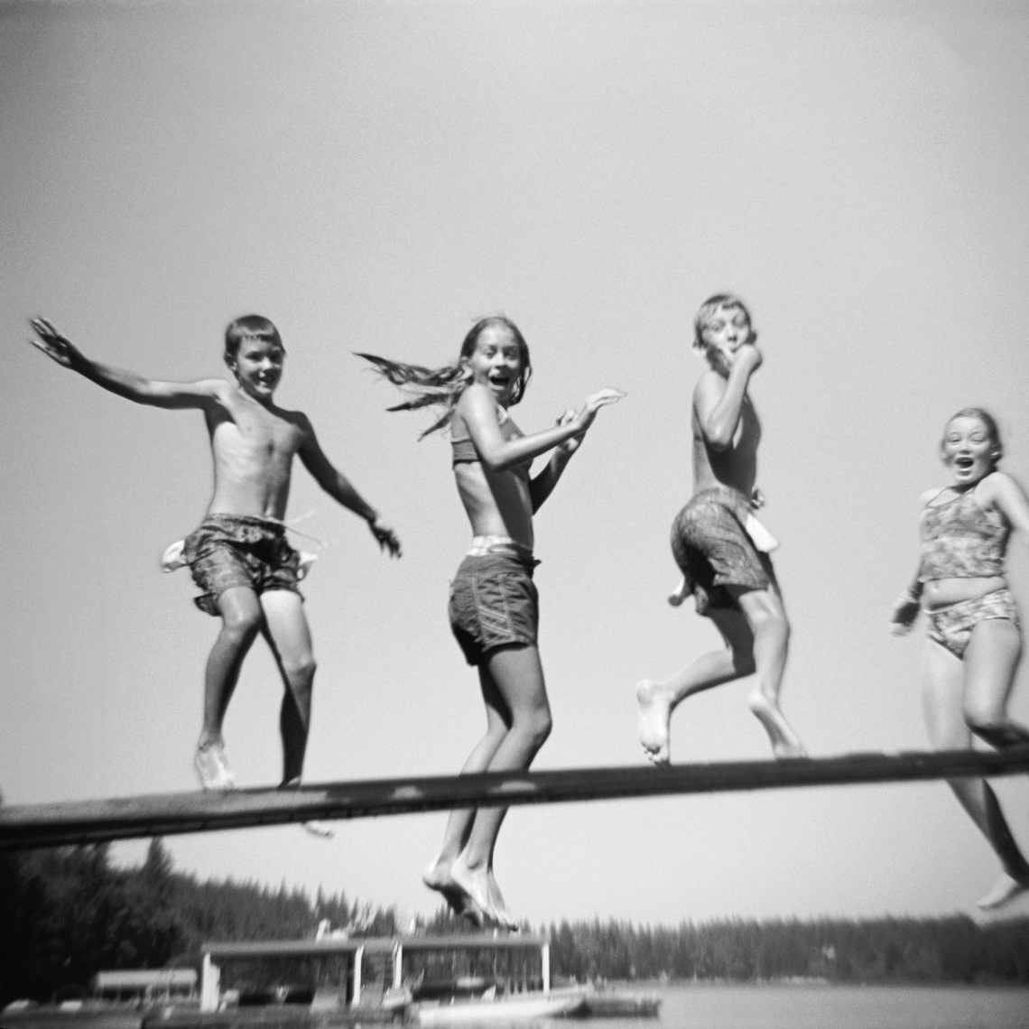 Black and white of Four kids jumping off a wooden diving board into a lake arms flailing