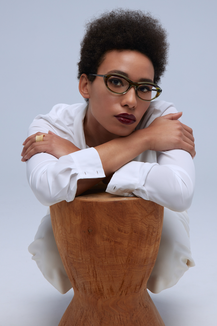 Curly haired woman in glasses and white blouse elbos on wood stool San Francisco fashion photographer