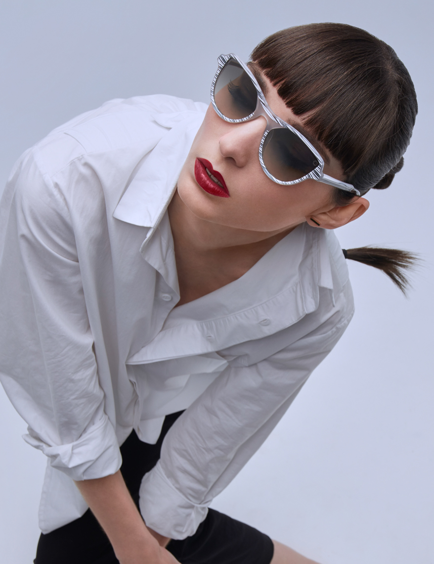 Woman in white blouse leaning with sunglasses and ponytail San Francisco fashion photographer