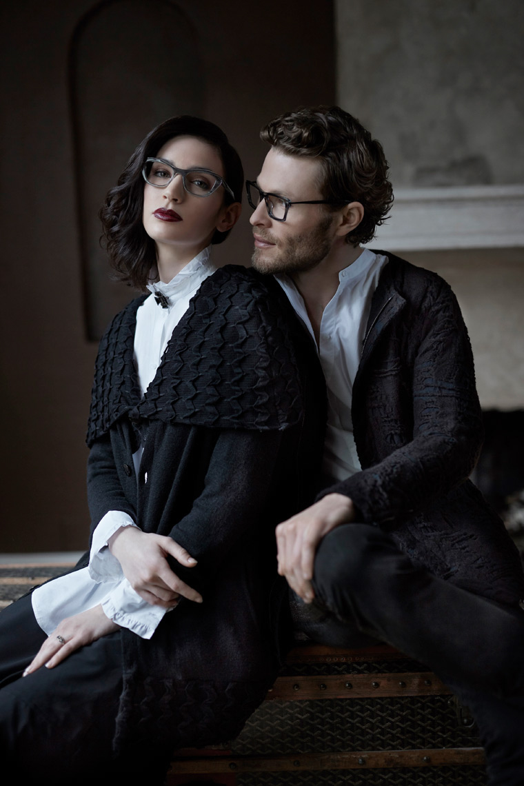 man with glasses holding and looking at woman with dark gown and eyewear