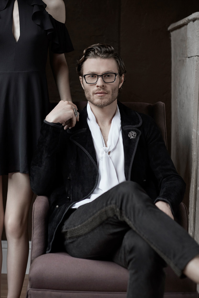 man in chair wearing casual suit and black frames with woman behind him San Francisco fashion photographer