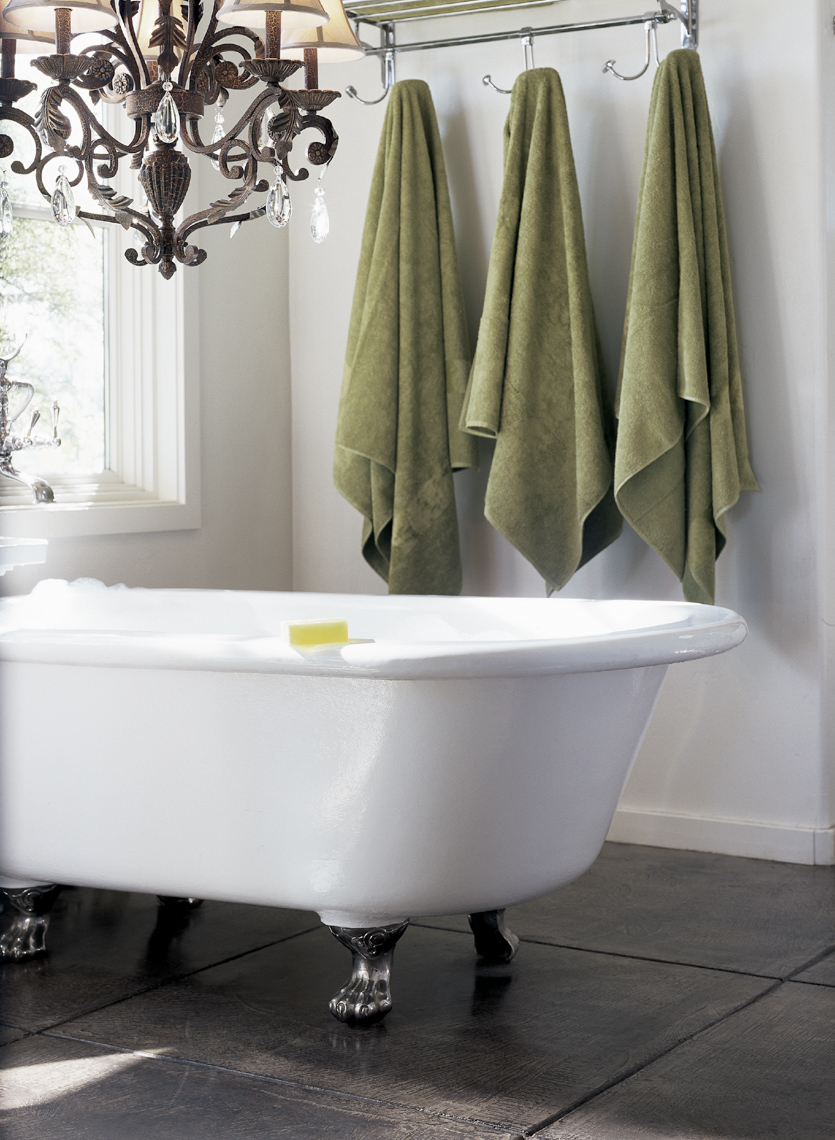 bathroom interior with white freestanding bathtub and 3 green hanging towels