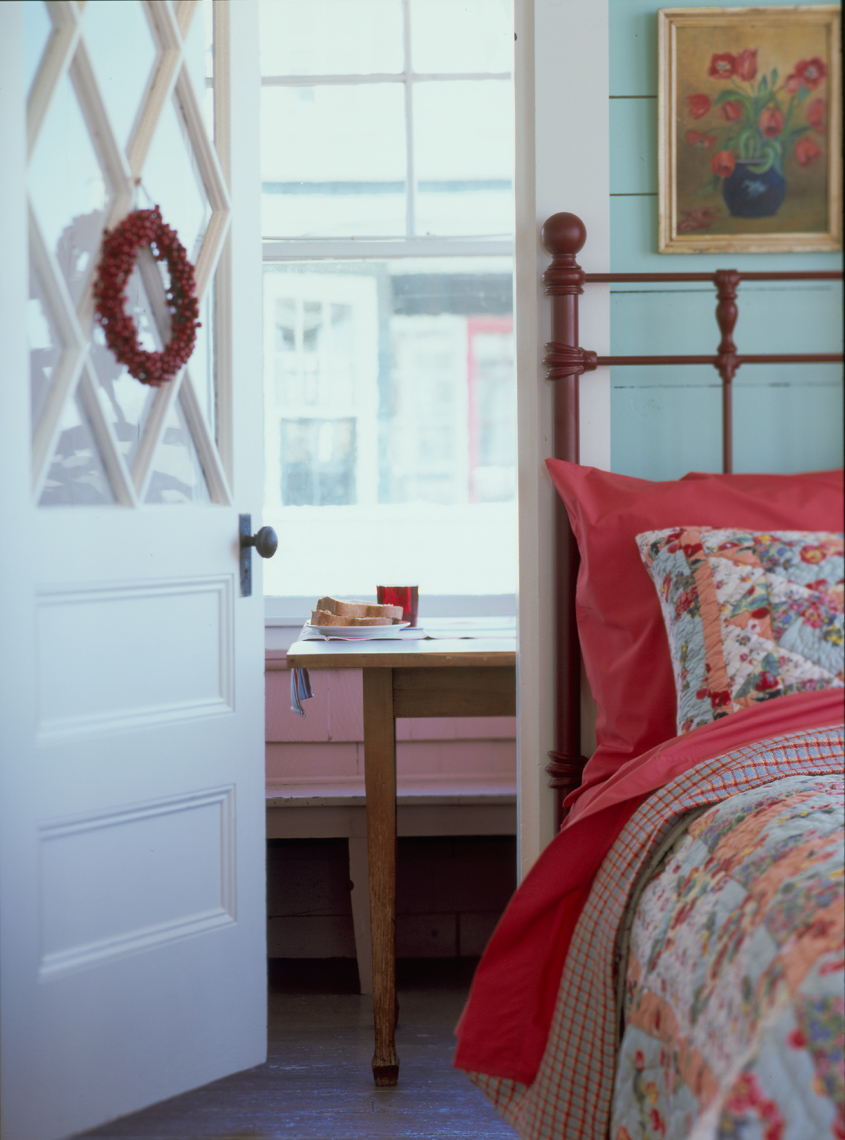 bedroom interior with floral quilt bedspread and view of dining table