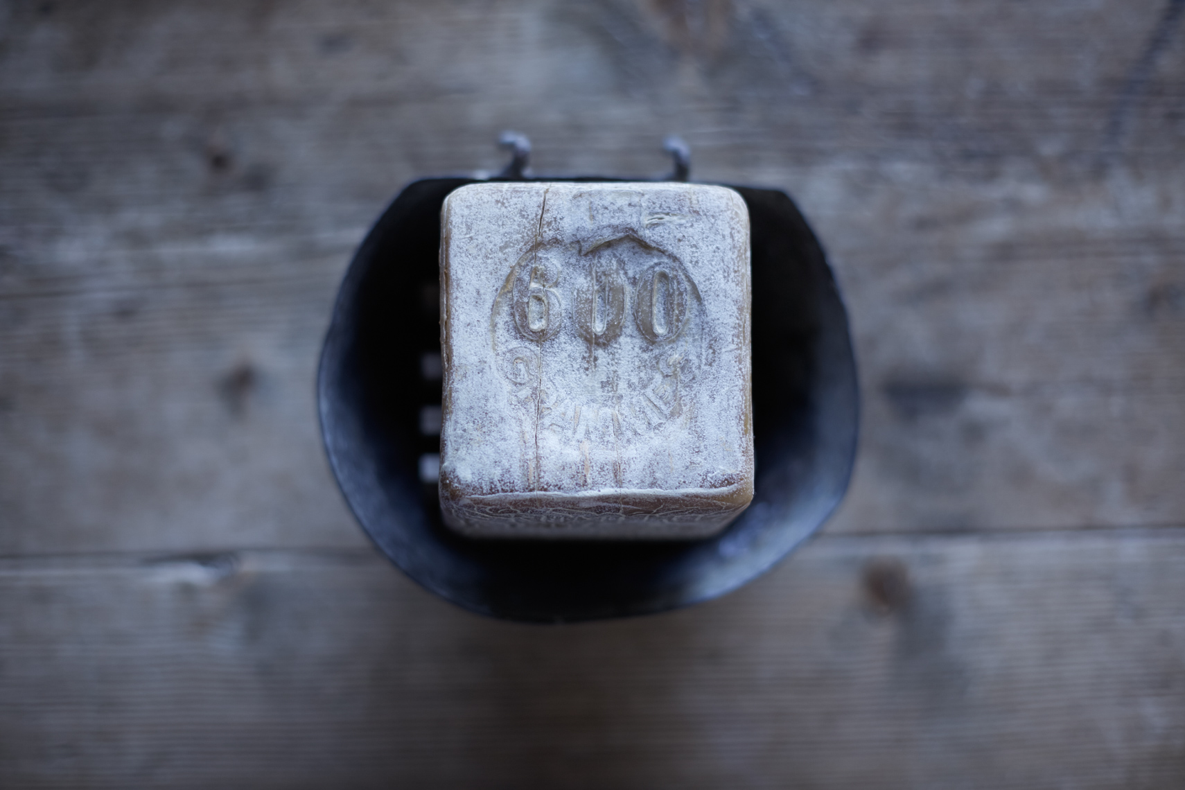detail of bar of soap on metal cup on wooden surface