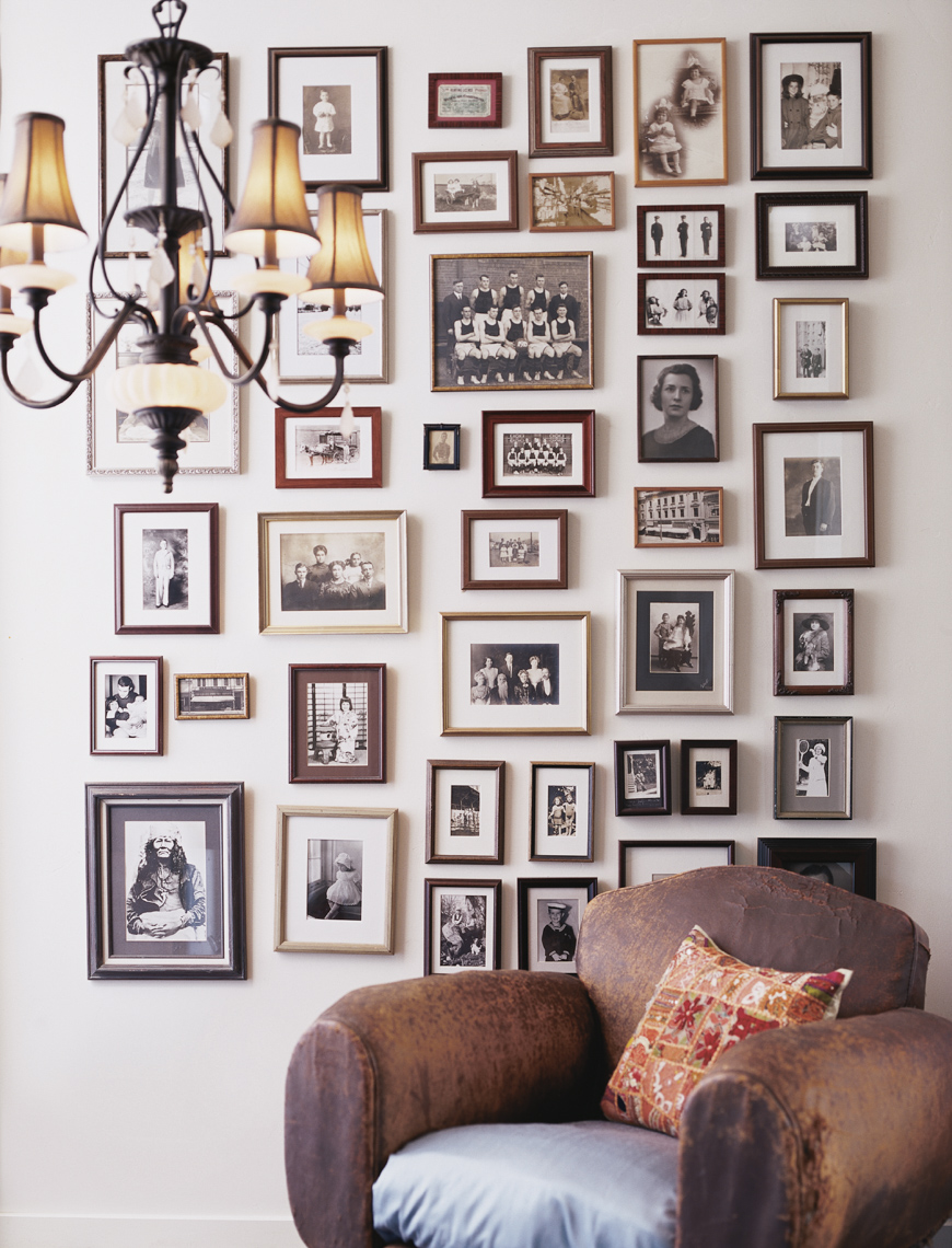 worn-leather armchair with wall of framed black and white photographs