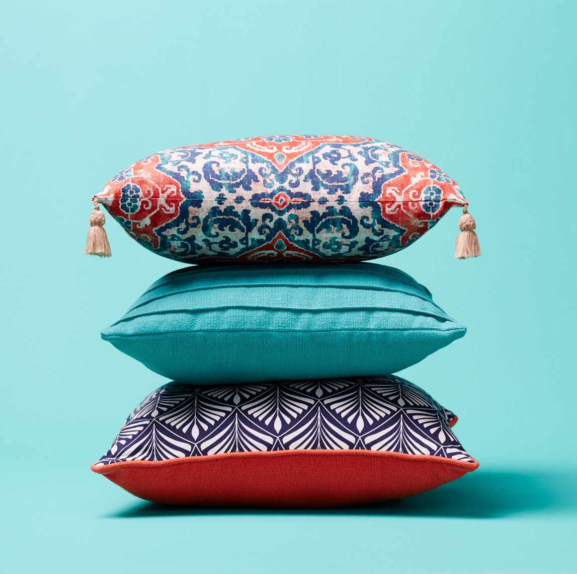 stack of blue and red patterned pillows with tassels and blue walls