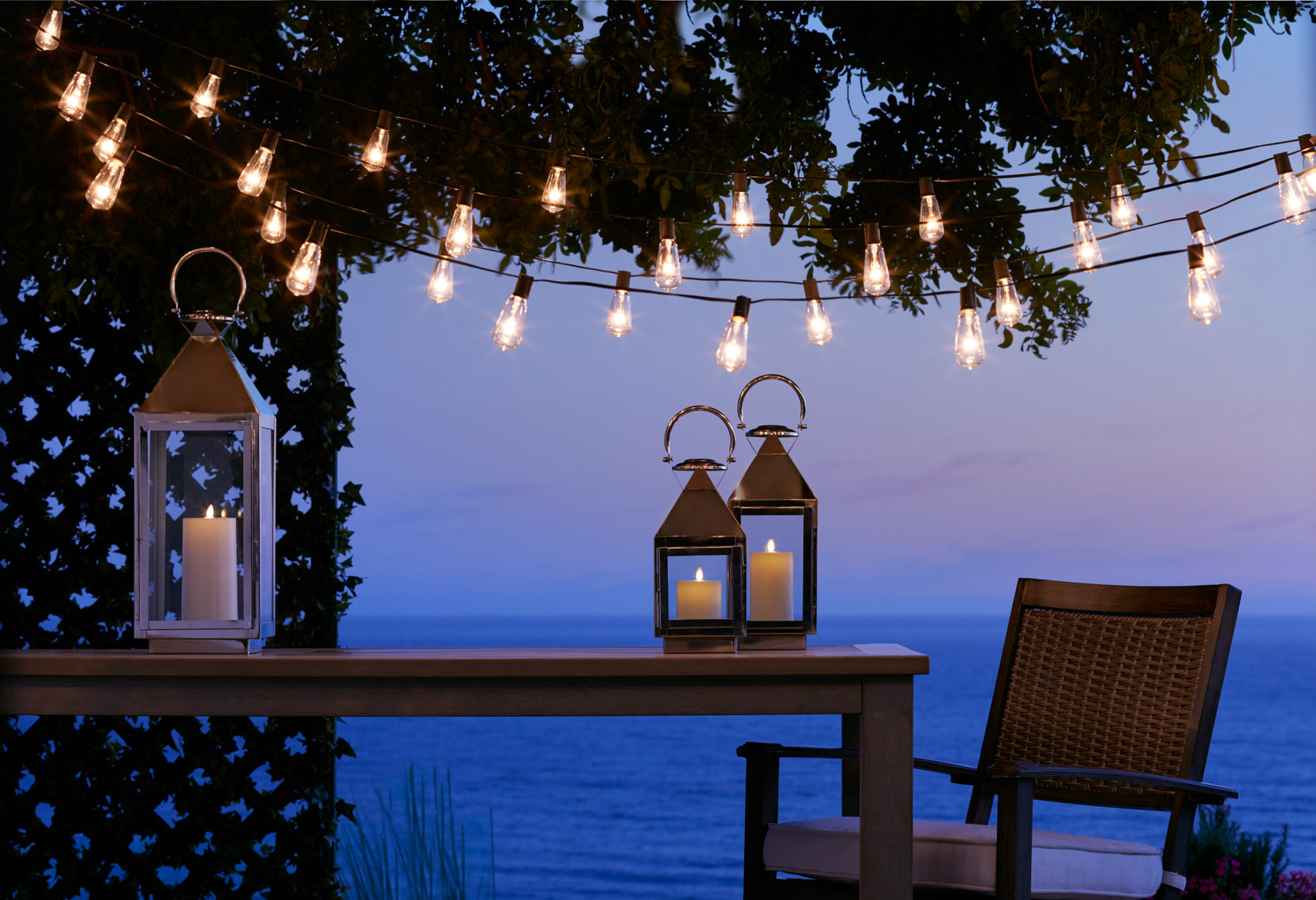 Glass and metal Lanterns with lit candles on wood table with string lights at dusk