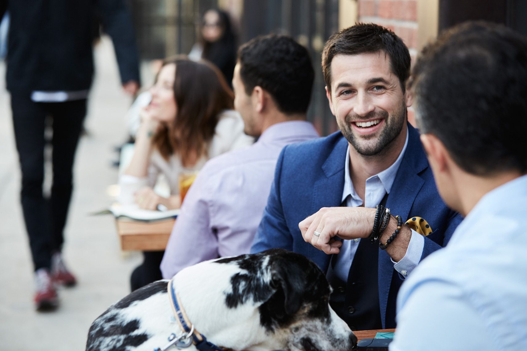 Bearded man in blue suit jacket at outdoor cafe table smiling while dog eats food from the plate on the table San Francisco lifestyle photographer