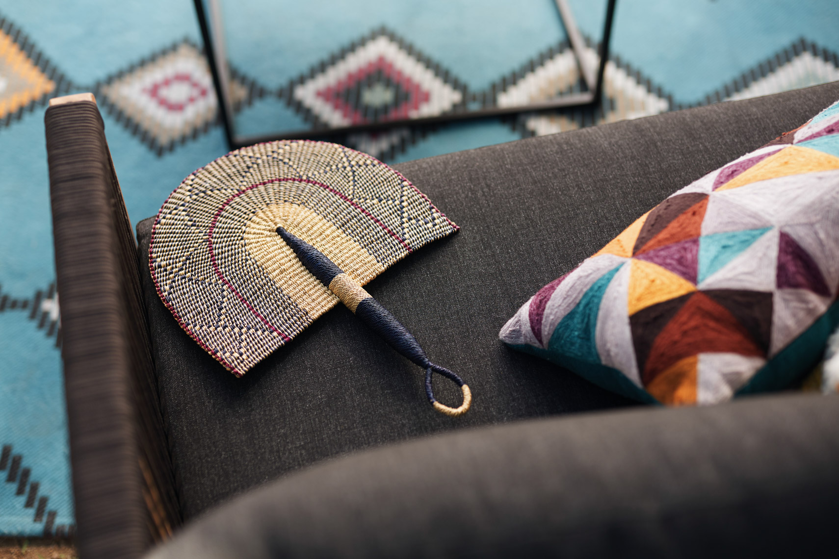 Detail of fan on dark couch with colorful pillow outside