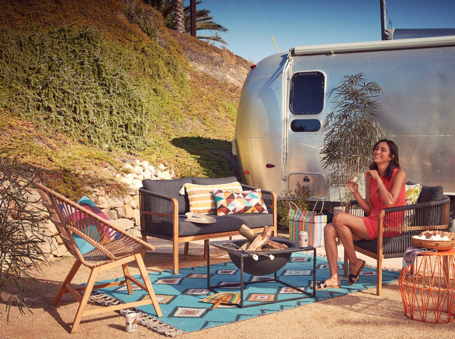 Woman laughing in orange drees seated at outdoor seating with fire bowl and Airstream trailer in the sun