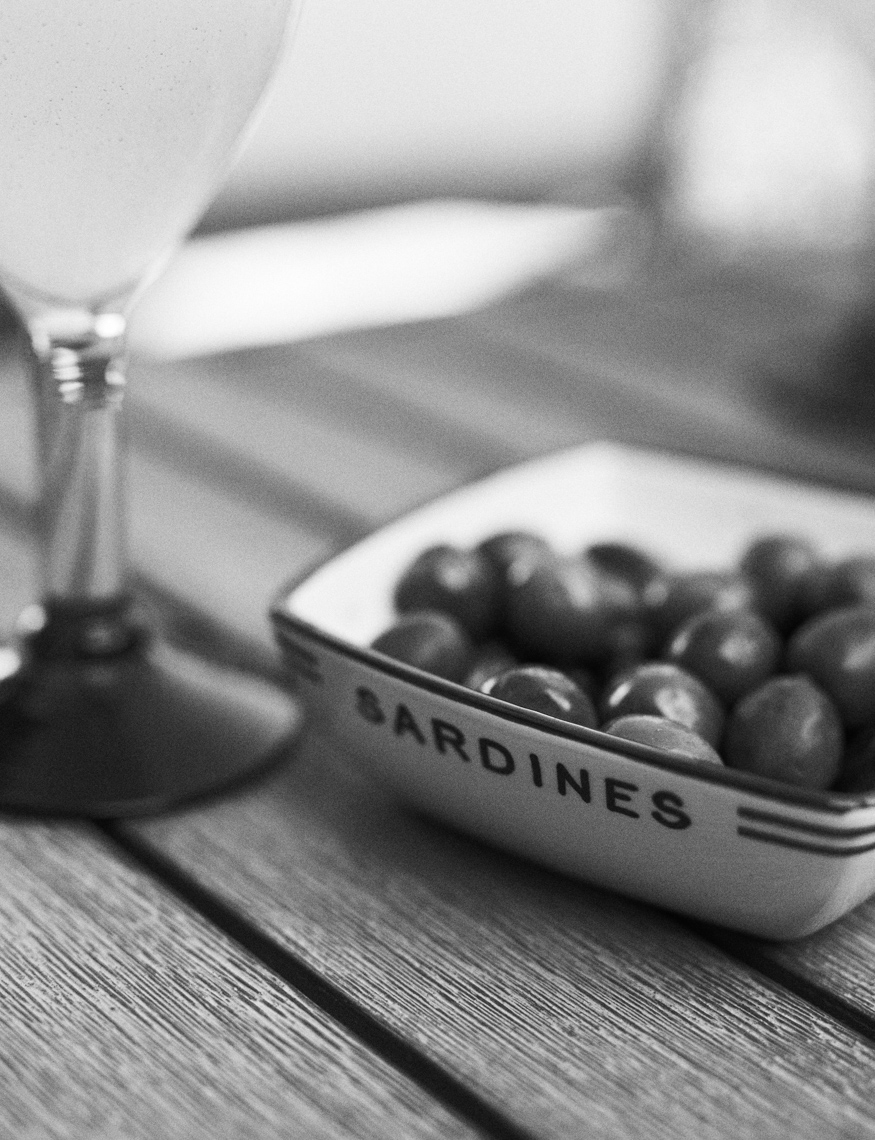 Black and white photo of white bowl of olives on wood table