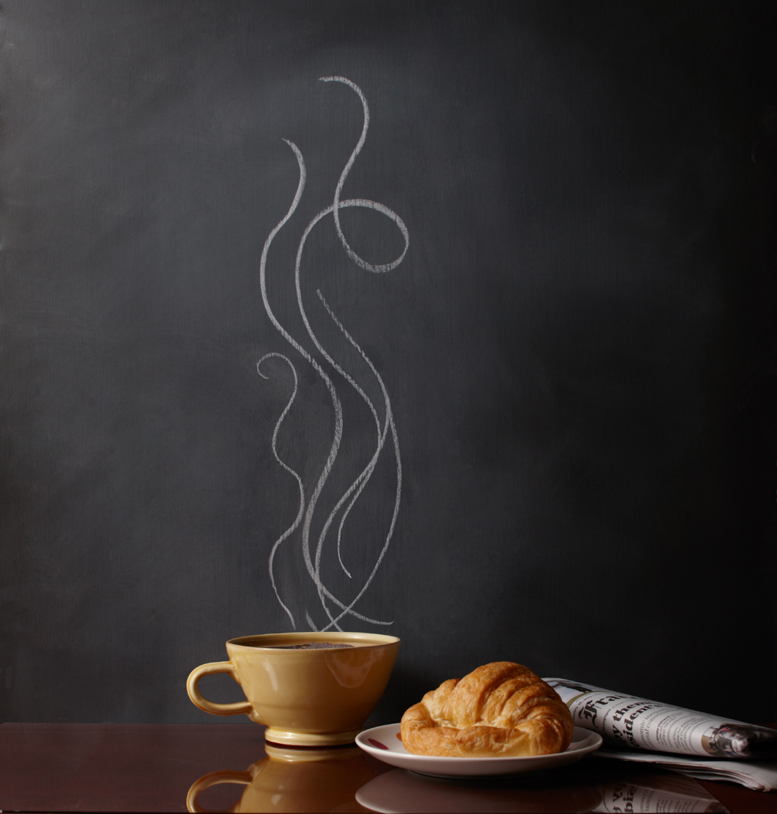 Yellow Coffee cup on wooden table with chalk-drawn steam and plate with crescent