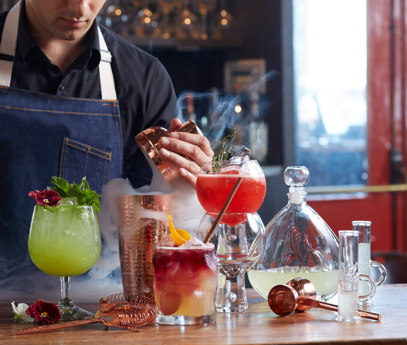 bartender using cocktail shaker and dry ice to make smoking drink with other martinis and beverages