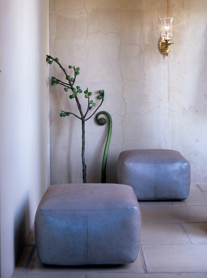 2 silvery-grey ottomans next to cracked marble wall San Francisco interior photographer