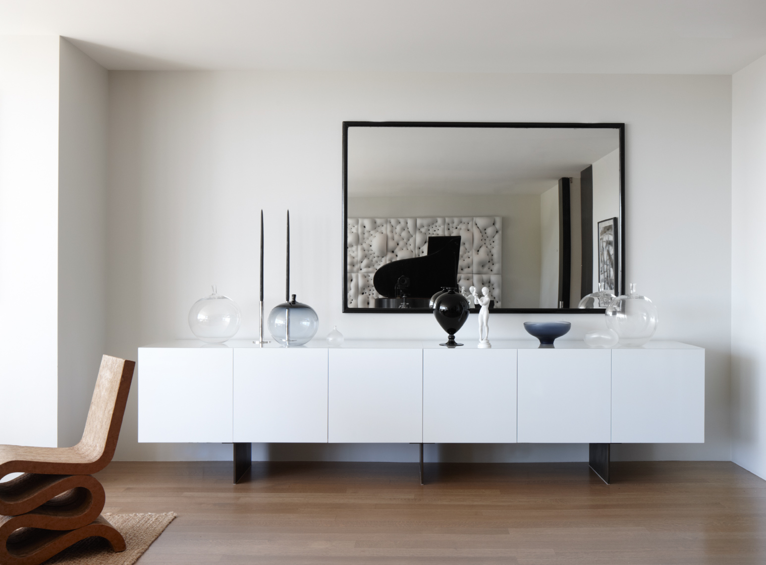 modern living room interior with white sideboard and glassware below a mirror