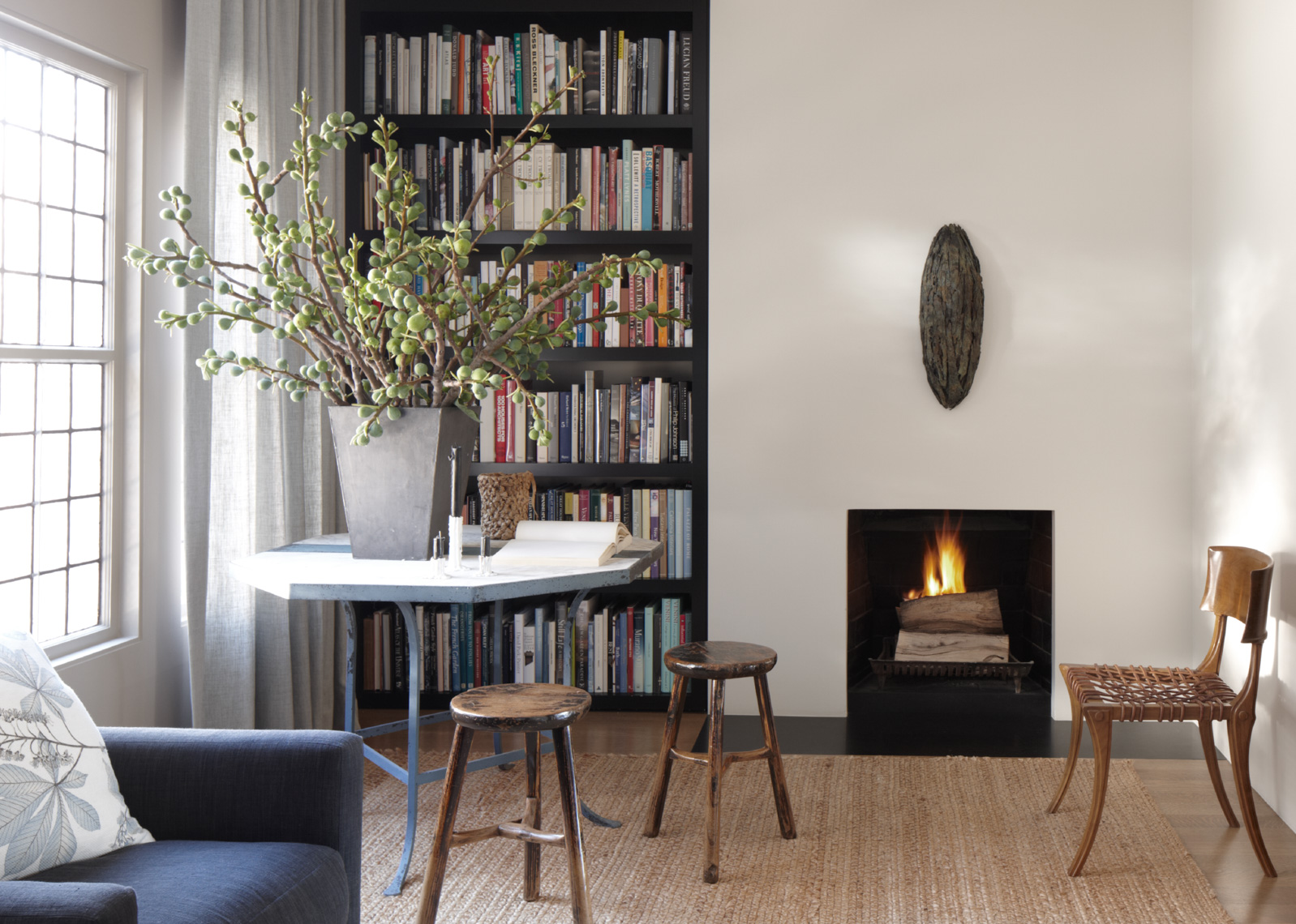 home interior with fireplace with wooden stools and bookshelf San Francisco interior photographer