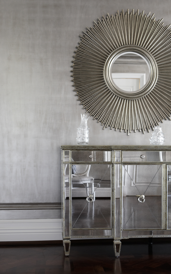 silver circular mirror with reflective cabinets