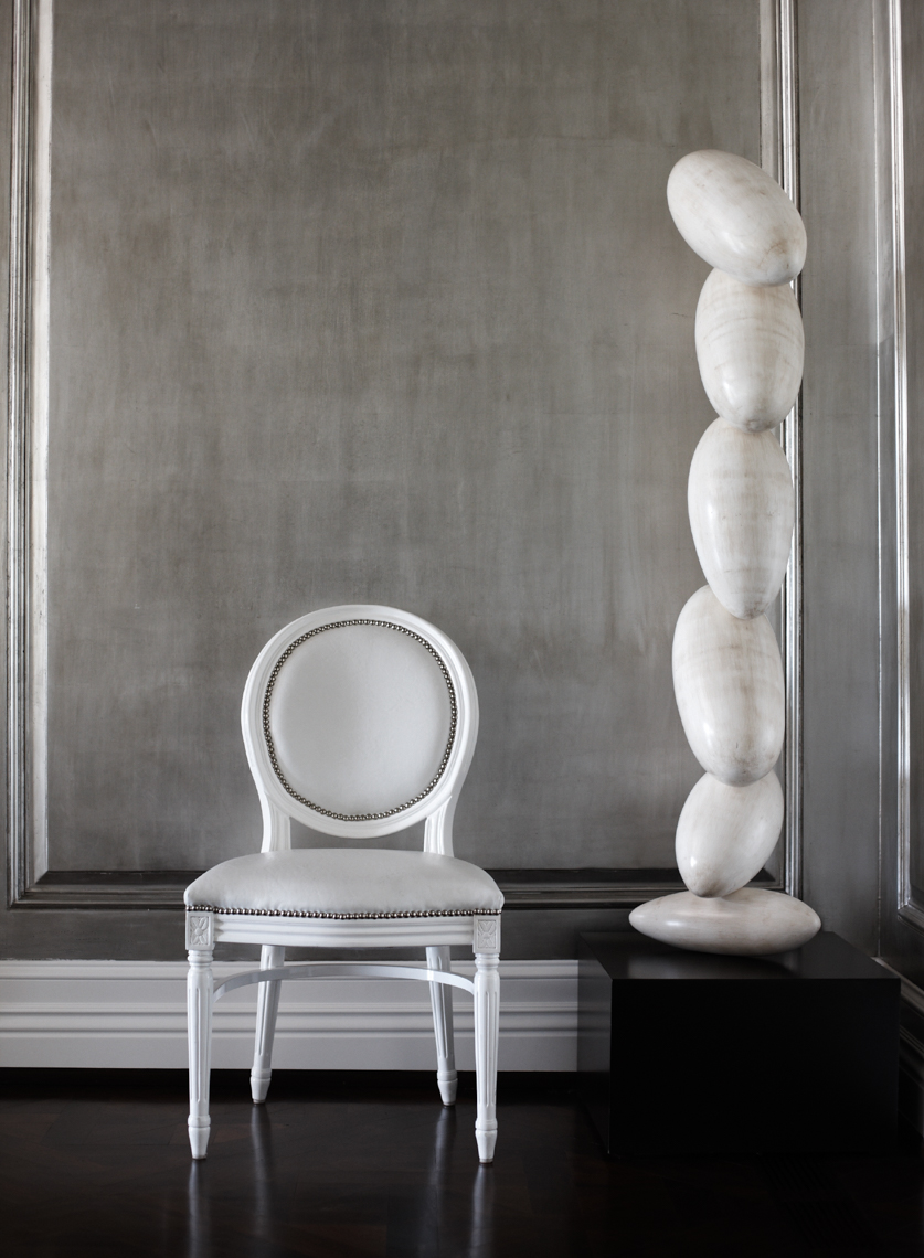 white round-back chair next to large white smooth stacked pebble sculpture with grey backdrop