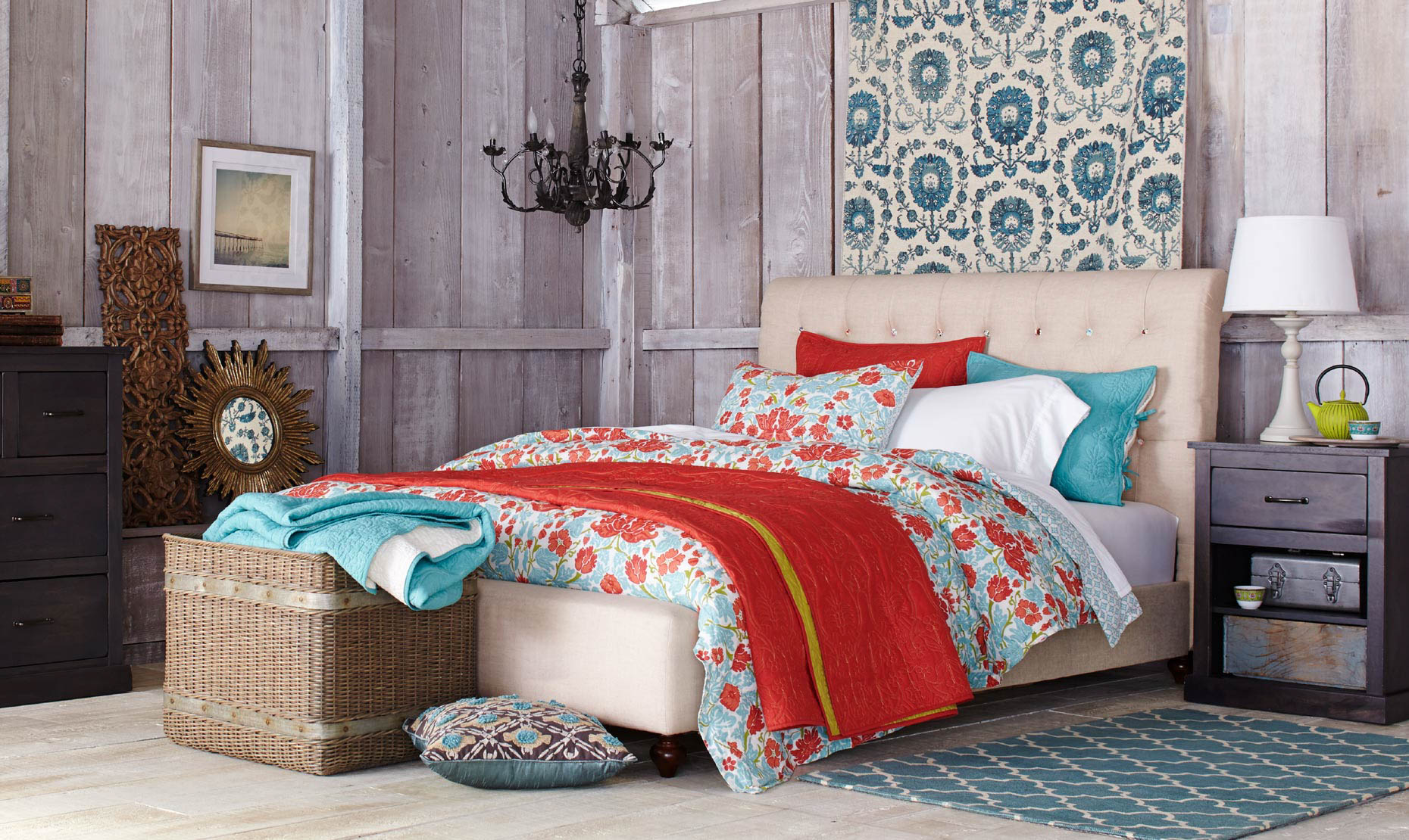 bedroom with red and blue floral print bedspread and blue rug and painting