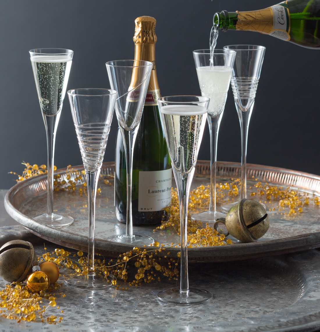 6 champagne flutes on a silver tray with 2 bottles of champagne