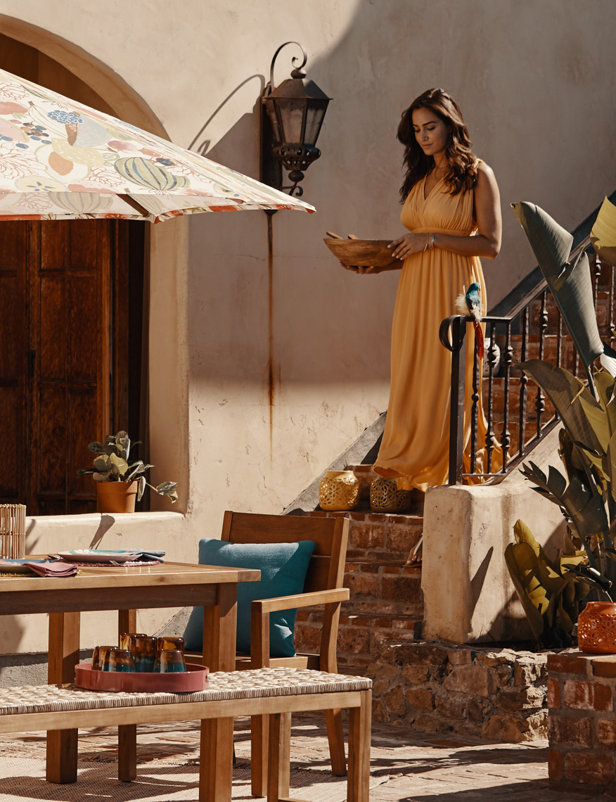 Woman in yellow dress carrying bowl to outdoor table with sun umbrella