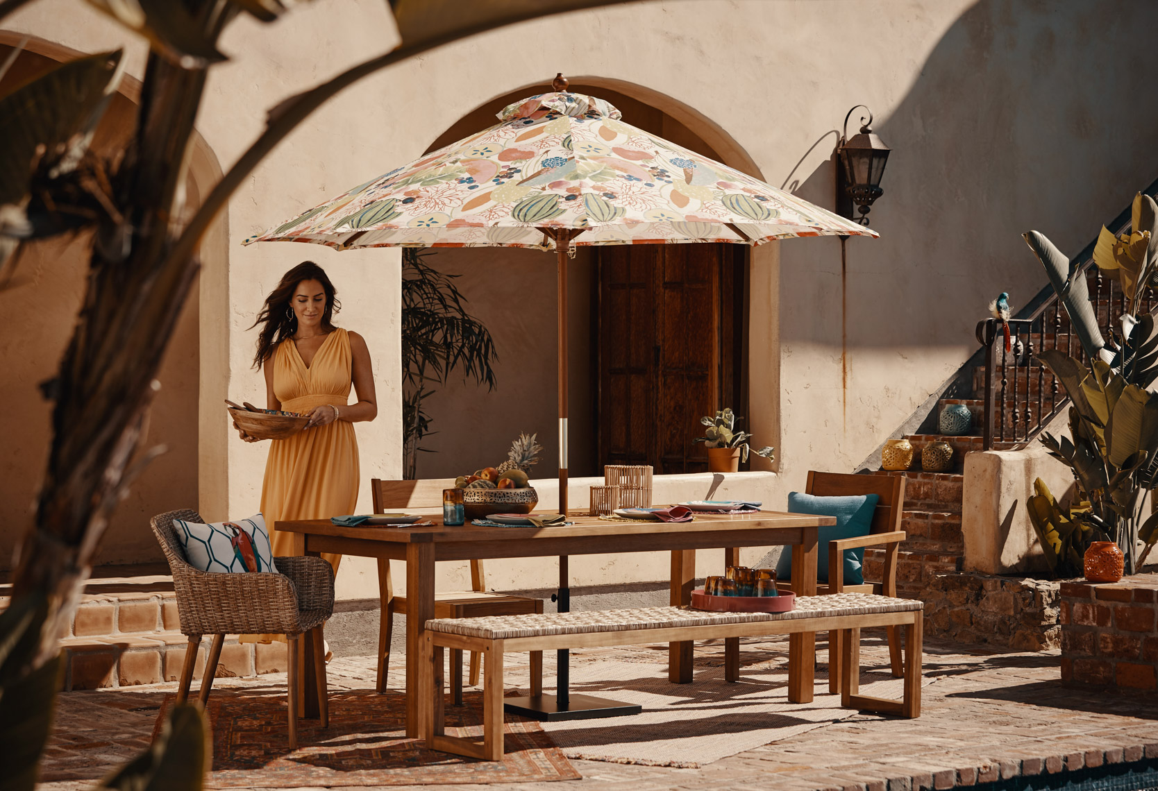 Woman in yellow dress carrying bowl to outdoor table with sun umbrella amd food on table