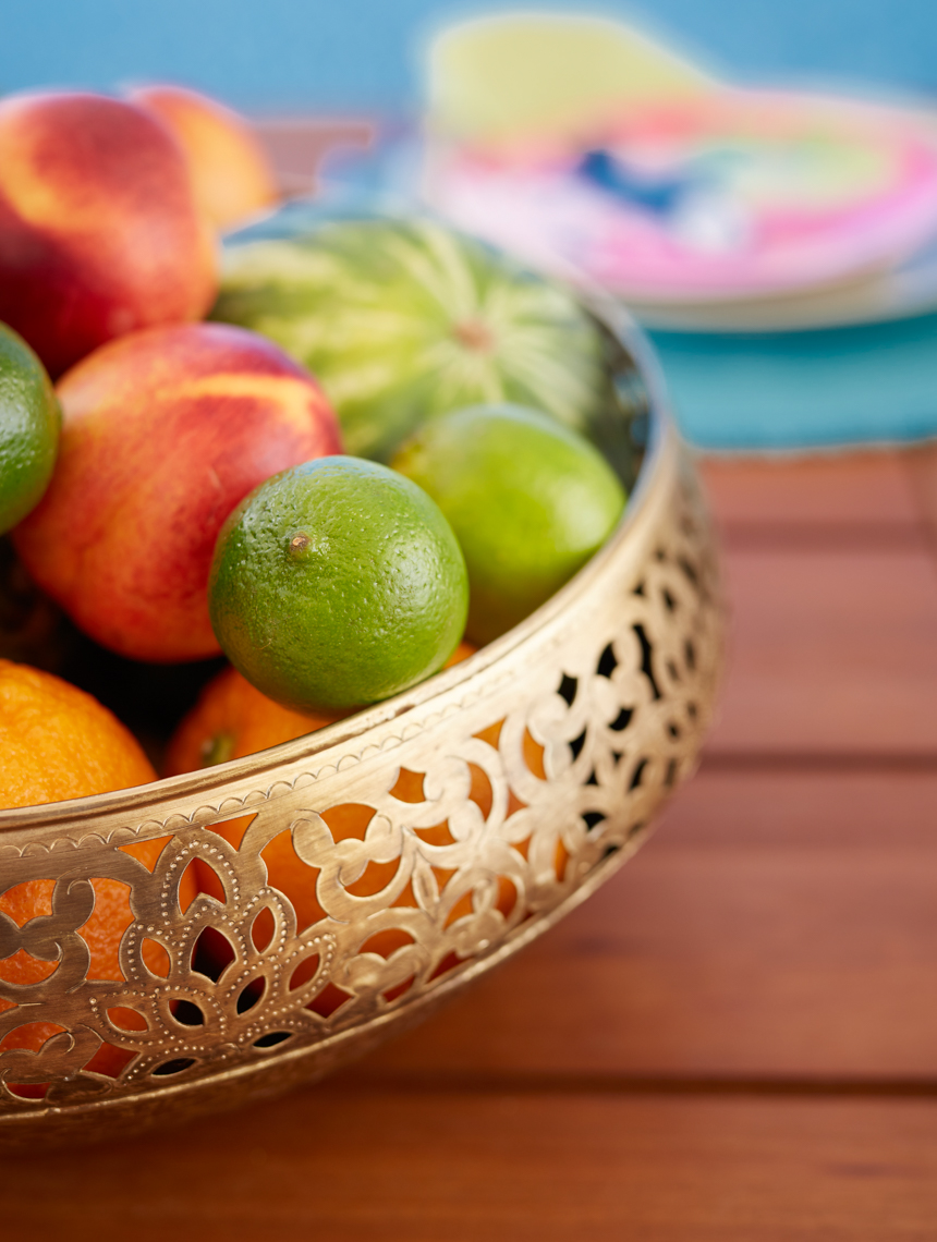 Gold metal bowl with tropical fruit on wood table outside