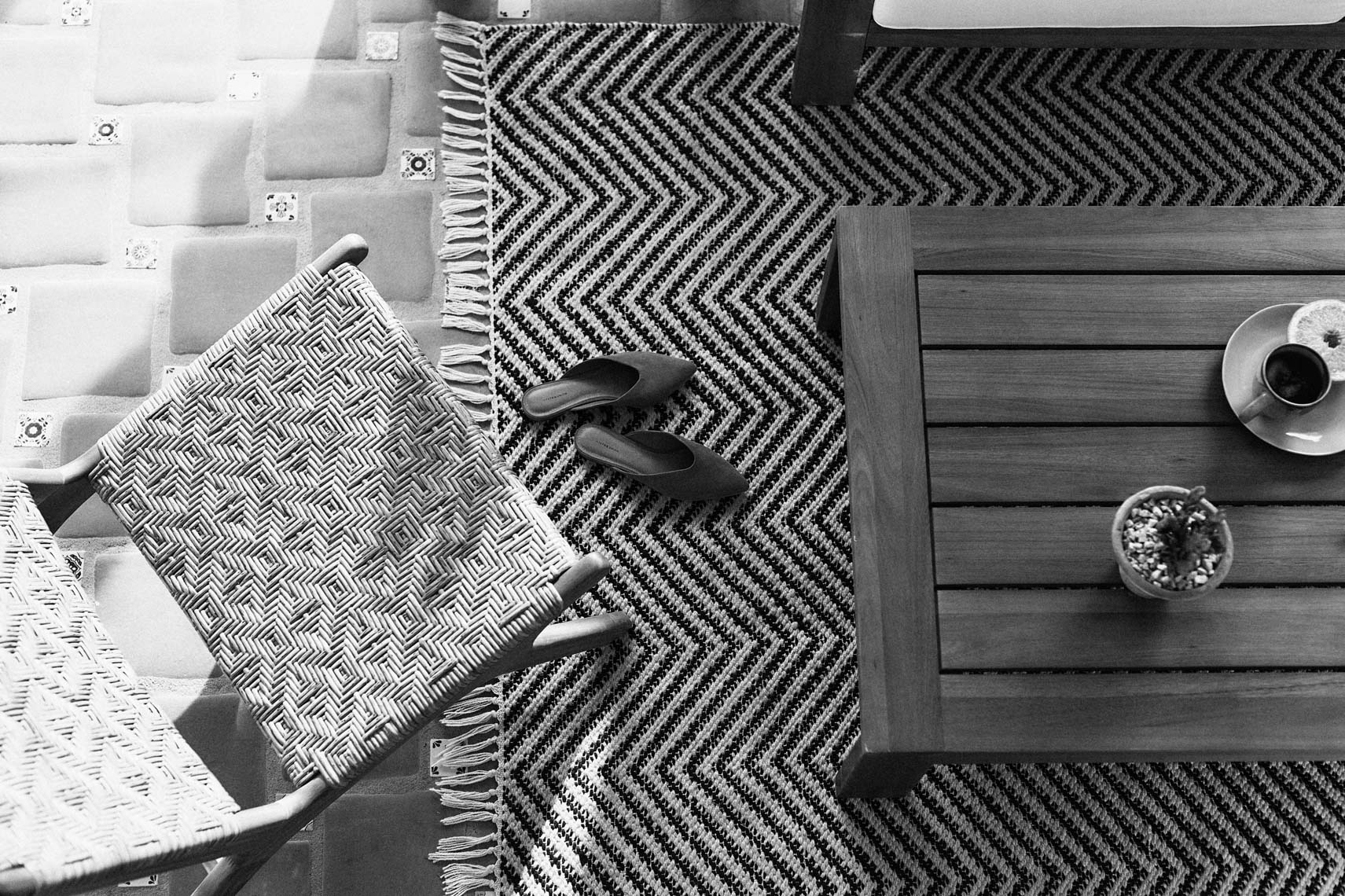 Straight down view of chair and table with shoes on pattern rug