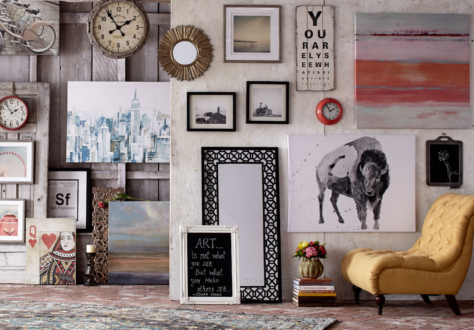 collection of mirrors and framed artwork on barn wall with yellow chair